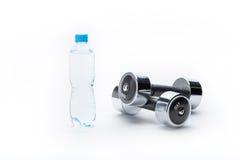 Металлические гантели и бутылка при вода изолированная на белизне Вода питья Стоковая Фотография RF