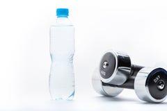 Металлические гантели и бутылка при вода изолированная на белизне Вода питья Стоковая Фотография
