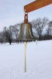 Металл колокол с полями Snowy зимы в предпосылке Стоковые Изображения RF