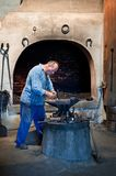 Металл кузнеца работая на наковальне в кузнице Стоковая Фотография
