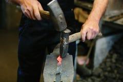 Металл кузнеца работая с молотком на наковальне в кузнице Стоковые Фото