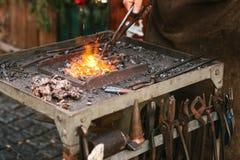 Металл кузнеца работая с молотком на наковальне в кузнице Стоковая Фотография RF