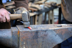 Металл кузнеца работая с молотком на наковальне Стоковое фото RF