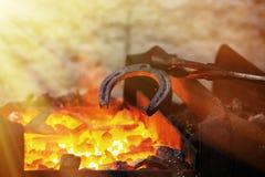 Металл кузнеца работая с молотком на наковальне Стоковое Изображение