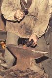 Металл кузнеца работая с молотком на наковальне Стоковые Фотографии RF