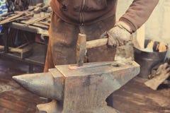 Металл кузнеца работая с молотком на наковальне Стоковая Фотография