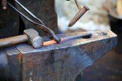 Металл кузнеца работая с молотком на наковальне Стоковое Фото