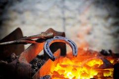 Металл кузнеца работая с молотком на наковальне Стоковые Изображения