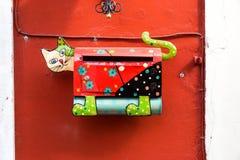 Металл почтового ящика сделанный в форме кота, на красной стене Стоковая Фотография