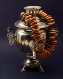 Металл самовара чая старый на темной предпосылке с бейгл Стоковые Фотографии RF
