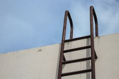 Металл старой лестницы вертикальный промышленный заржавел к цистерне с водой Стоковые Изображения