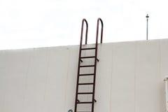 Металл старой лестницы вертикальный промышленный заржавел к цистерне с водой Стоковые Изображения RF