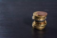 Металл стога евро монеток европейца красит черноту стола валюты Стоковое Изображение RF