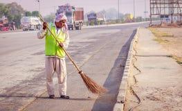 Метельщик очищая дорогу с веником