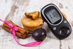 Метр глюкозы, булочки с сливами и ручками циннамона на деревенской доске, диабете и очень вкусной концепции десерта стоковые фотографии rf