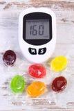 Метр глюкозы для измеряя уровня сахара и красочных конфет, концепции помадок еды уменьшения стоковые фотографии rf