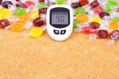 Метр глюкозы для измеряя уровня сахара, конфет и раздробленного коричневого тростникового сахара стоковые фото