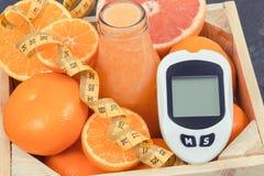 Метр глюкозы для измеряя уровня сахара, свежо смешанное coctail от цитруса и сантиметр Диабет, уменьшая и здоровый стоковые изображения