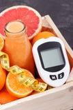 Метр глюкозы для измеряя уровня сахара, свежо смешанное coctail от цитруса и сантиметр Диабет, уменьшая и здоровый стоковое фото