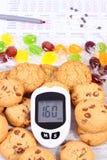 Метр глюкозы, красочные конфеты с печеньями на медицинской форме, диабетом, концепцией помадок еды уменьшения стоковое изображение rf