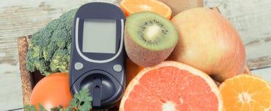 Метр глюкозы со здоровыми фруктами и овощами Проверяющ уровень сахара, диабет, диета и уменьшающ концепцию стоковые изображения rf