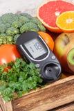 Метр глюкозы со здоровыми фруктами и овощами Проверяющ уровень сахара, диабет, диета и уменьшающ концепцию стоковое фото rf