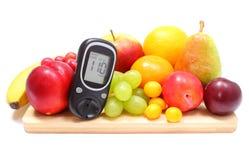 Метр глюкозы и свежие фрукты на деревянной разделочной доске Стоковые Изображения