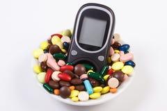 Метр глюкозы с кучей медицинских пилюлек и капсул, диабета, концепции здравоохранения стоковая фотография rf