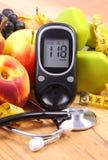 Метр глюкозы с медицинскими стетоскопом, плодоовощами и гантелями для использования в фитнесе стоковое изображение