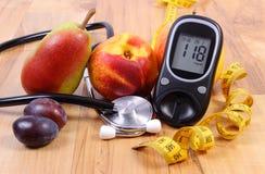 Метр глюкозы с медицинским стетоскопом и свежими фруктами, здоровым образом жизни стоковая фотография