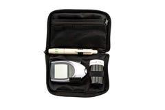 Метр содержания глюкозы в крови, значение уровня сахара в крови измерен на пакете пальца в черном случае на белой предпосылке Сох стоковое изображение