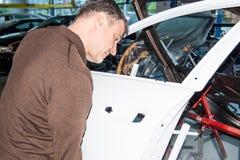 Механики автомобиля выравнивают bonnet правильно собирая - мастерская ре стоковая фотография rf