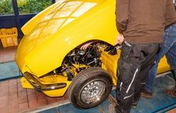 Механики автомобиля выравнивают bonnet правильно собирая - мастерская ре стоковое фото rf