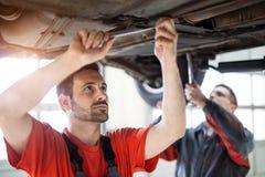 Механики автомобиля работая на автомобильном пункте обслуживания стоковое фото rf