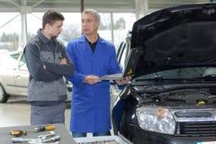 Механики обсуждая рядом с автомобилем в гараже Стоковые Фотографии RF