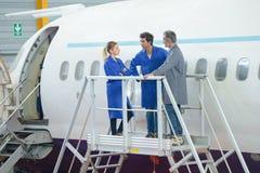 Механики проверяя взлет двигателя самолетов avant стоковые изображения rf