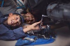 механики Работники скрепляет болтами гайки семьи принципиальной схемы состава стоковое изображение rf
