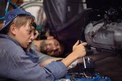 механики Работники скрепляет болтами гайки семьи принципиальной схемы состава стоковые изображения