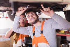 Механики ремонтируя автомобиль клиента стоковое фото