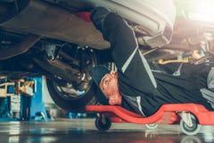 Механик автомобиля под автомобилем стоковые фотографии rf