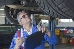 Механик анализируя двигатель автомобиля на ремонтной мастерской ремонта автомобилей Стоковое фото RF