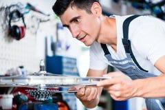Механик велосипеда работая в его мастерской велосипеда Стоковое Изображение RF