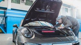 Механик в гараже автомобиля проверяя клобук роскоши sportcar Стоковые Фотографии RF