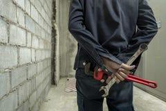 Механик в ключе металла фабрики стоя на предпосылке фабрики стоковые фото
