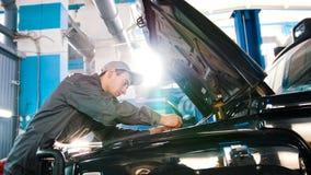 Механик в обслуживании автомобиля - ремонтирующ в машинном отсеке для роскоши SUV Стоковые Фотографии RF