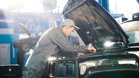 Механик в обслуживании автомобиля - ремонтирующ для роскоши SUV Стоковые Изображения RF