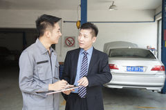 Механик гаража объясняя к клиенту, показывая ему Билл Стоковые Фото
