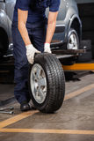Механик держа автошину автомобиля на гараже Стоковые Фото