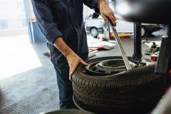 Механик извлекая автошину от оправы на машине Стоковое Фото