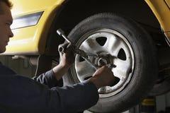 Механик изменяя автомобиль катит внутри гараж Стоковые Изображения